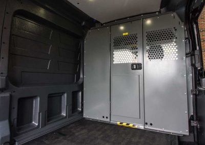 Ford Transit cargo van bulkhead partition with perforated view-through areas.